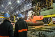 Steelworkers watching hot steel casting on crane in steelworks - CUF37953