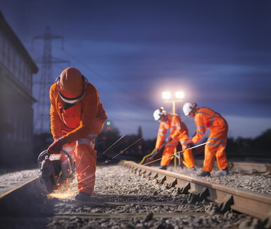 Railway maintenance workers using grinder on track at night - CUF37998