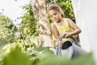 Girl concentrating whilst watering plants in garden - CUF38049