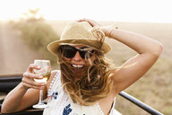 Young woman wearing hat holding glass of wine - ISF15170