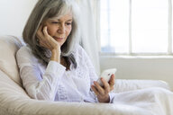 Senior woman looking at smartphone - ISF15179