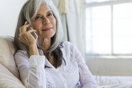Portrait of attractive senior woman chatting on smartphone - ISF15233