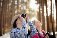 Two mature women bird watching in forest - ISF15245
