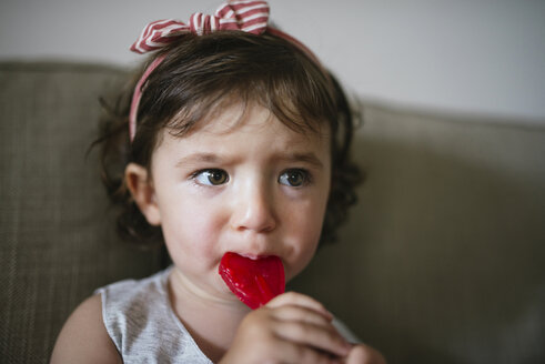 Cute baby girl eating a heart shaped lollipop at home - GEMF02099