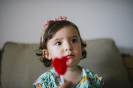 Cute baby girl eating a heart shaped lollipop at home - GEMF02105