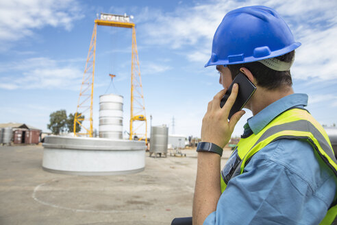 Man in workwear on construction site talking on cell phone - ZEF15749