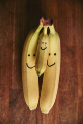 Bunch of two large and one small bananas with smiley faces - RHF02032