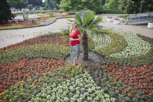 Happy pregnant woman standing amidst blooming flowers in park - RHF02053