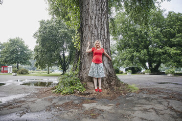 Portrait of smiling pregnant woman standing at a tree in park - RHF02059