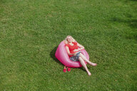 Happy pregnant woman sitting in inflatable seat on meadow - RHF02062