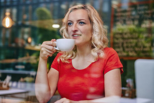 Portrait of smiling blond woman drinking coffee in a cafe - RHF02071