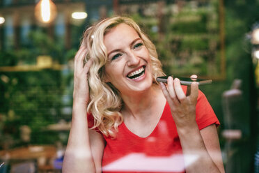 Portrait of laughing blond woman using smartphone in a cafe - RHF02074
