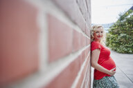 Portrait of smiling pregnant woman outdoors leaning against a brick wall - RHF02080