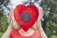 Woman holding a heart-shaped vinyl record outdoors - RHF02086