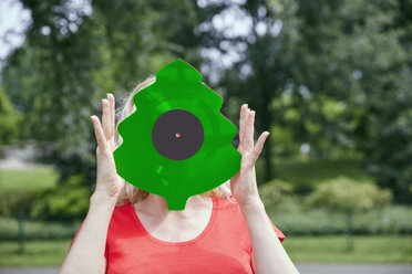 Woman holding a Christmas tree shaped vinyl record outdoors - RHF02089