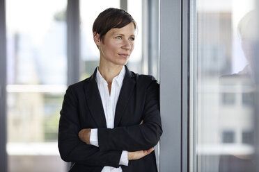 Businesswoman in office looking out of window - RBF06358