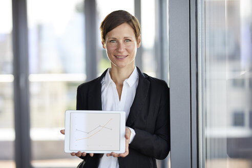 Portrait of smiling businesswoman in office holding tablet showing ascending line graph - RBF06361