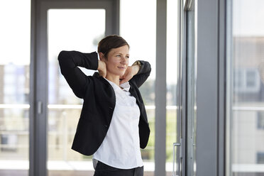 Businesswoman in office looking out of window - RBF06367