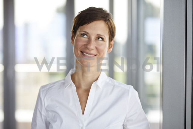 Portrait of smiling businesswoman in office looking up - RBF06370 - Rainer Berg/Westend61