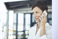 Portrait of smiling businesswoman on cell phone - RBF06373