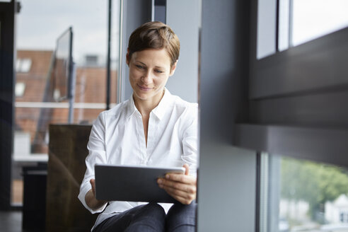 Businesswoman sitting in office at the window using tablet - RBF06379