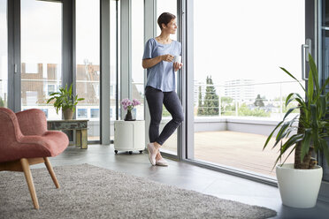Woman at home with cup of coffee looking out of balcony door - RBF06385
