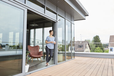 Woman at home with cup of coffee looking on roof terrace - RBF06388