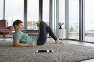 Woman lying on the floor at home with tablet looking out of balcony door - RBF06391
