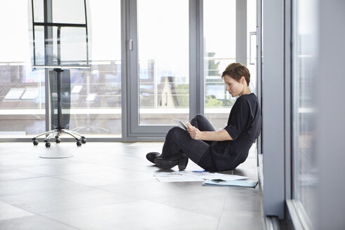 Businesswoman sitting on the floor in office using tablet - RBF06403