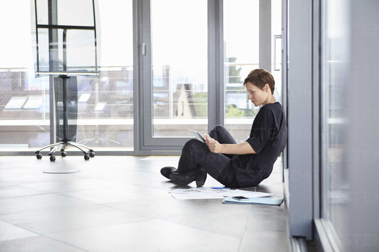 Businesswoman sitting on the floor in office using tablet - RBF06403 - Rainer Berg/Westend61
