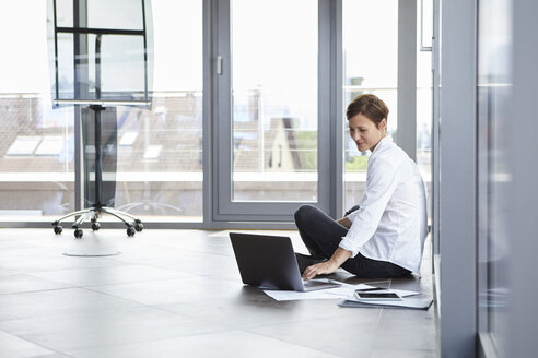 Businesswoman sitting on the floor in office using laptop - RBF06406