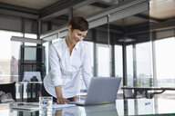 Smiling businesswoman standing at glass table in office looking at laptop - RBF06412