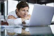 Businesswoman leaning on glass table in office looking at laptop - RBF06415