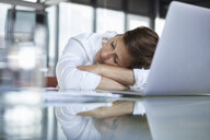 Businesswoman with closed eyes lying on glass table in office in front of laptop - RBF06418
