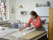 Woman working on glass pane in glazier's workshop - BFRF01865