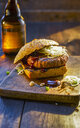 Burger on wooden board next to beer bottle - KSWF01926