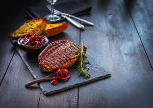 Beefsteak with rosemary, red wine onions and garlic bread on slate - KSWF01947