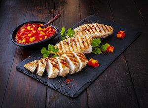 Chicken breast fillet with bell pepper chutney on slate - KSWF01950