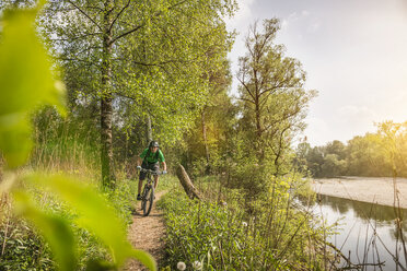 Young man cycling along riverside path - CUF38097