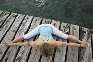 Overhead view of mid adult woman with arms and legs outstretched practicing yoga on wooden sea pier - CUF38115