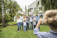 Boy taking photo of three generational family in garden - CUF38199
