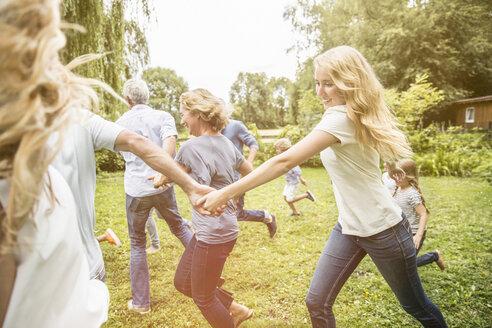 Family running in garden - CUF38205