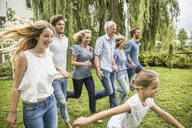 Three generational family running in garden - CUF38208