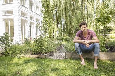 Young man sitting in garden - CUF38238