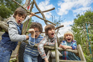 Four boy shouting on homemade climbing frame in garden - CUF38259