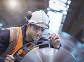 Engineer measuring steel part in engineering factory - CUF38292