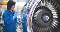 Female engineer working on engine in aircraft maintenance factory - CUF38310
