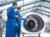 Engineers discussing engine in aircraft maintenance factory - CUF38313