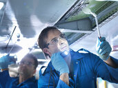 Engineers working on aircraft wing in aircraft maintenance factory, close up - CUF38316