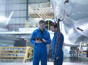 Engineers using digital tablet and in discussion in aircraft maintenance factory - CUF38322